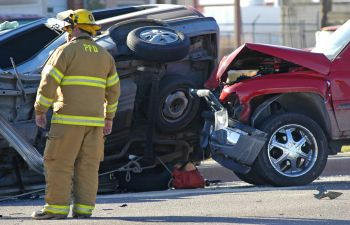 a firefighter next to two vehicles involved in a head-on collision