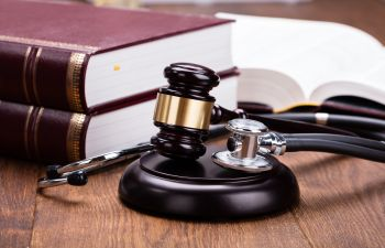 judge's gavel and stethoscope next to legal books
