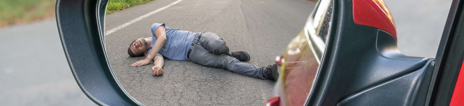 a man hit by a car lying on the road