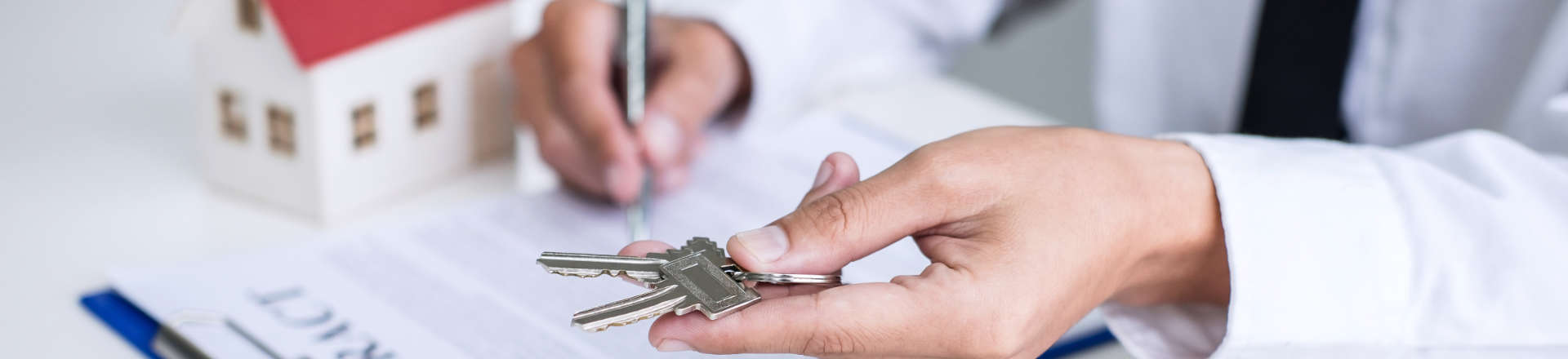 a man holding house keys and signing documents