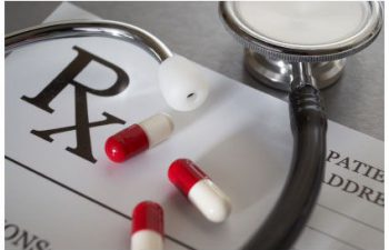 medicines, a stethoscope and a blank prescription